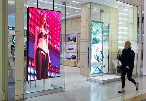 Indoor LED window screen with customer walking past